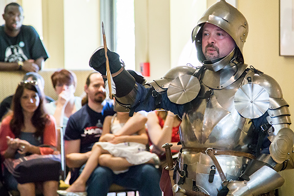 An educator dressed in medieval armor during a public presentation