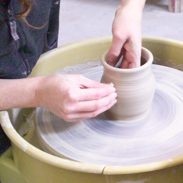 A clay pot being made on a potter's wheel