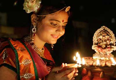 A girl lighting clay Diwali lamps