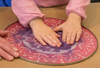 Making Rangoli sand art with a stencil