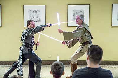 Two men demonstrating combat with lightsabers
