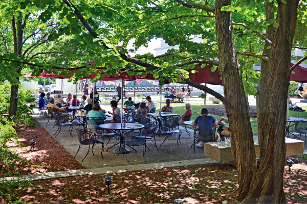 View of Museum visitors sitting in the Stoddard Garden and enjoying refreshments in the shade