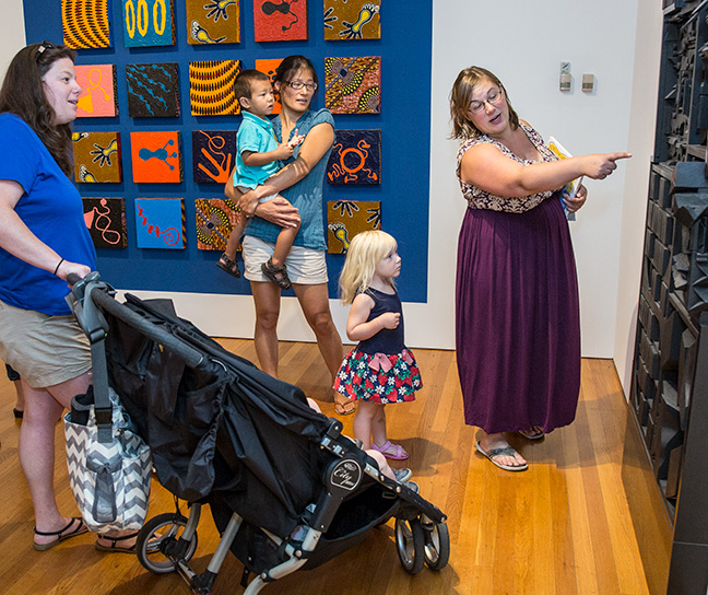 A tour group including parents with young children and strollers explore a gallery