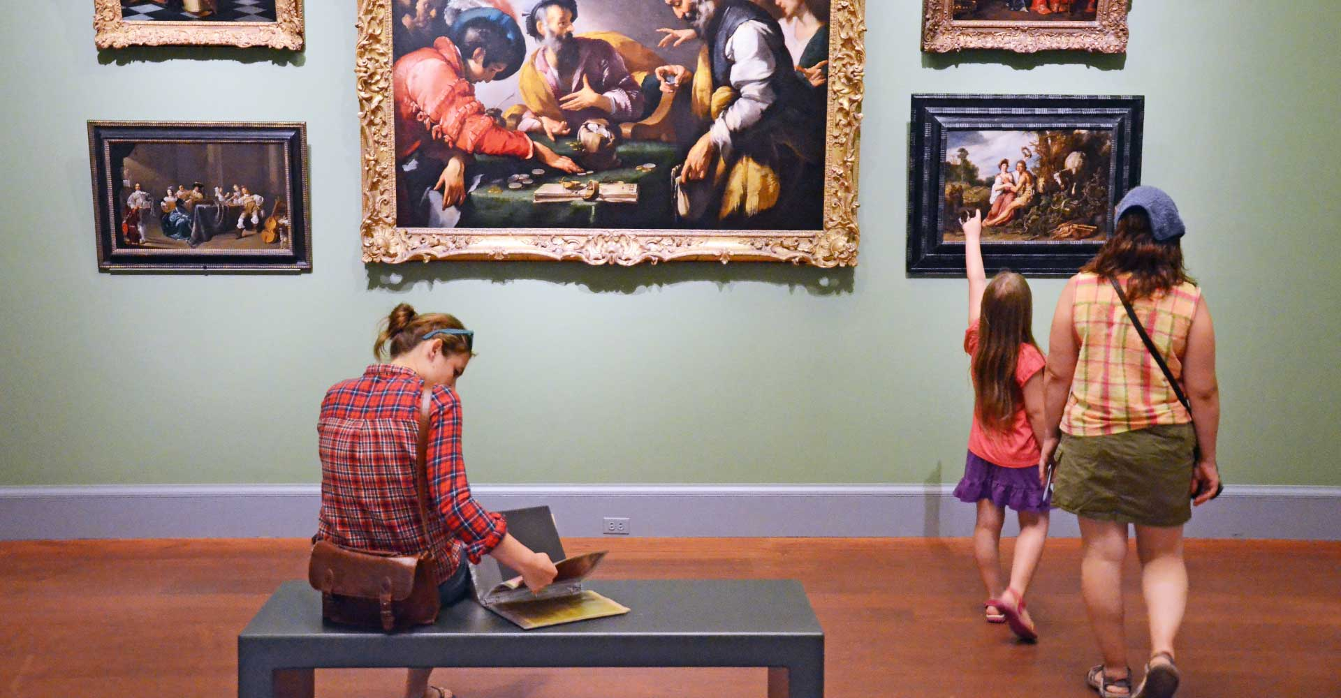 Visitors enjoy paintings in a European gallery
